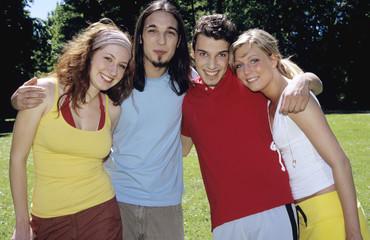Vier junge Leute stehen im Garten, Portrait