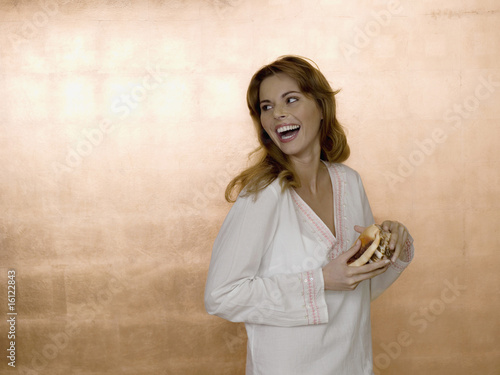 Woman holding shell, laughing