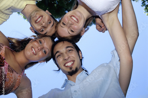 Four young people in huddle, upward view, portrait