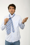 Young businessman getting ready, adjusting tie, close-up, portrait