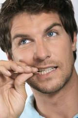 Junger Mann mit Zahnstocher zwischen den Zähnen, close-up
