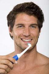 Junger Mann halten elektrische Zahnbürste