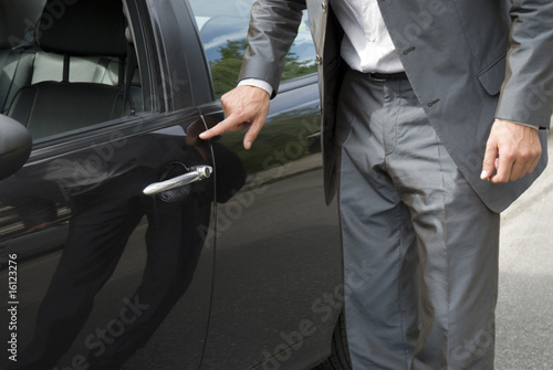 Businessman examining car, close-up, mid section
