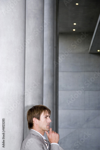 Businessman standing with hand on chin, side view