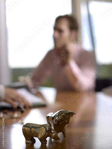 Figurines of bull and bear on desk (focus on foreground)