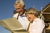 Senior couple holding plan in front of partially built house