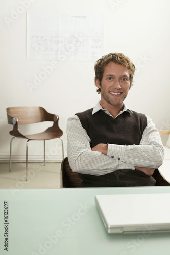 Young man sitting by desk with laptop, arms crossed, smiling, portrait