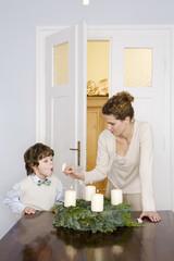 Mutter und Sohn anzünden Adventskranz