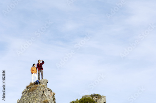 Young couple standing on mountain peak, looking away