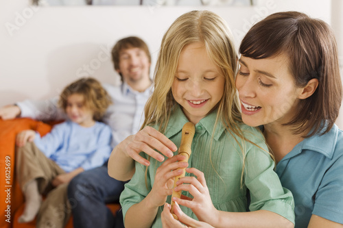 Mother and daughter (8-9), playing recorder