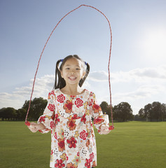 Young girl outdoors jumping rope