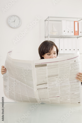 Businesswoman reading newspaper, portrait