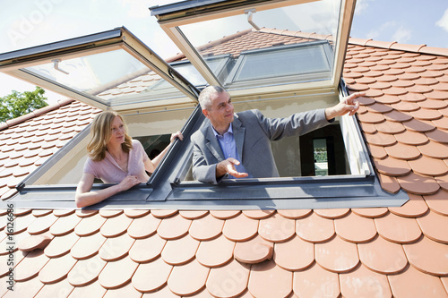 Couple looking out dormer windows, man pointing