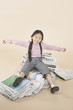 Young girl sitting on pile of newspapers indoors