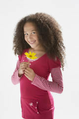 Young girl indoors holding a flower