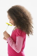 Young girl indoors smelling a flower