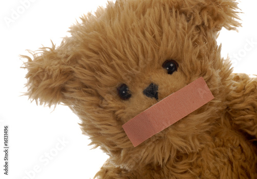 stuffed teddy bear with bandaid on mouth