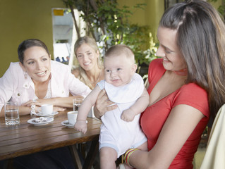 Three women on outdoor patio where one is holding a smiling baby