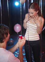 Man proposing to smiling woman in nightclub