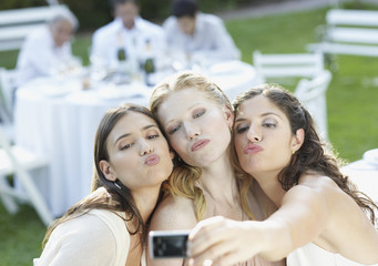 Three women at an outdoor party taking a self-portrait with a digital camera and puckering up