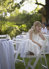 Young girl crouched on chair at outdoor party smiling