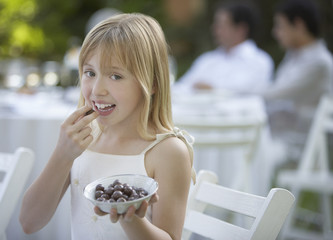 Young girl at outdoor party eating olives