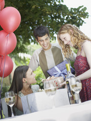 Partygoers at outdoor party giving gifts to woman and smiling
