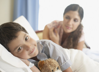 Young boy in hospital bed smiling with woman looking over him