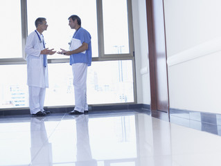 Two doctors standing in hospital corridor talking