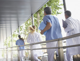 Four hospital workers running down corridor