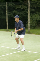 active healthy retired senior man playing tennis