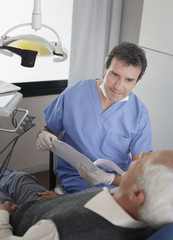 Dentist in examination room with patient holding chart