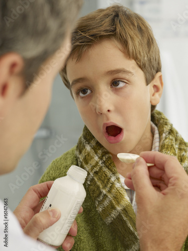 Doctor giving young patient medicine