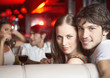 Couple sitting together in booth at nightclub smiling