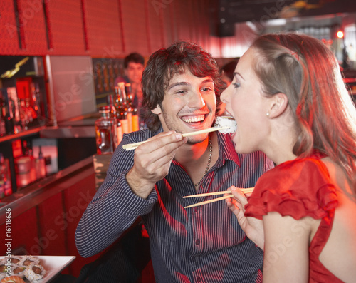 Man feeding woman sushi in nightclub and smiling