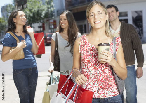 Four friends outdoors carrying shopping bags and smiling