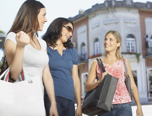 Three women outdoors with shopping bags smiling