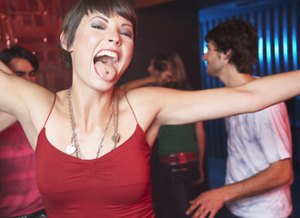 Woman in nightclub sticking her tongue out with people dancing behind her smiling