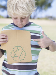 Young boy holding piece of cardboard with recycle symbol and pointing