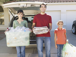 Man and woman with young girl outdoors standing in driveway holding recyclable materials and smiling