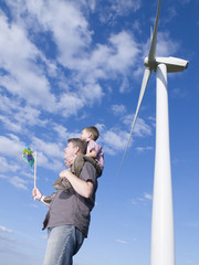 Man holding toy windmill with young boy on shoulders standing by real windmill outdoors