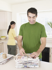 Man in kitchen binding up newspapers and smiling
