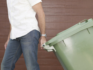 Man outdoors pulling garbage bin