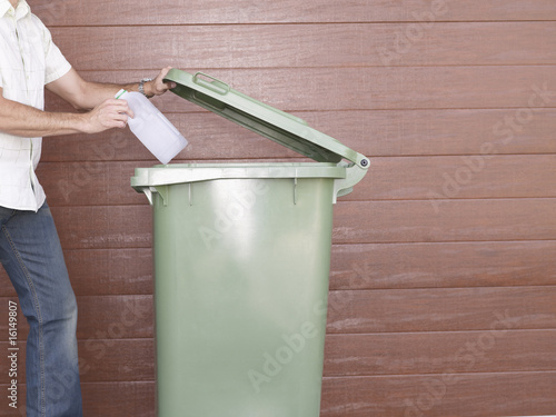 Man outdoors putting plastic bottle into garbage bin