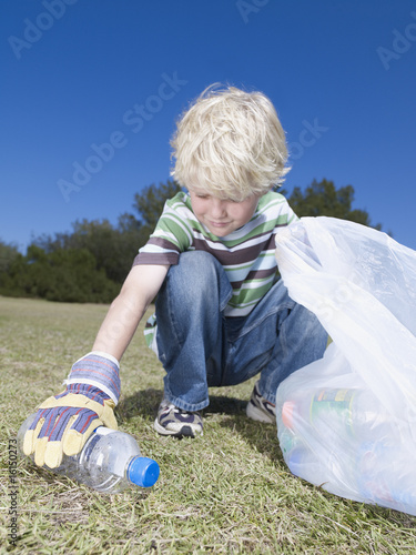 Young boy outdoors picking up empty plastic bottle to put into bag