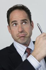 View of a businessman thinking and holding a pen.