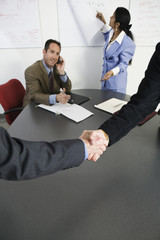 View of businessmen shaking hands in an office.
