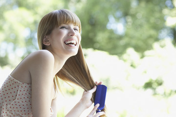 Woman outdoors brushing hair and laughing