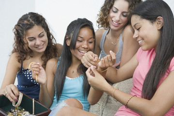 Teen girls playing with jewelry