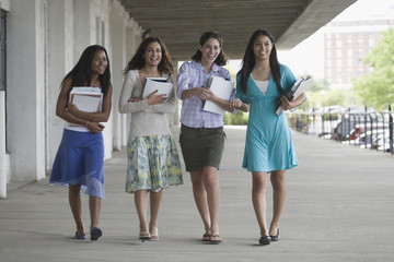 Four teen female students walking